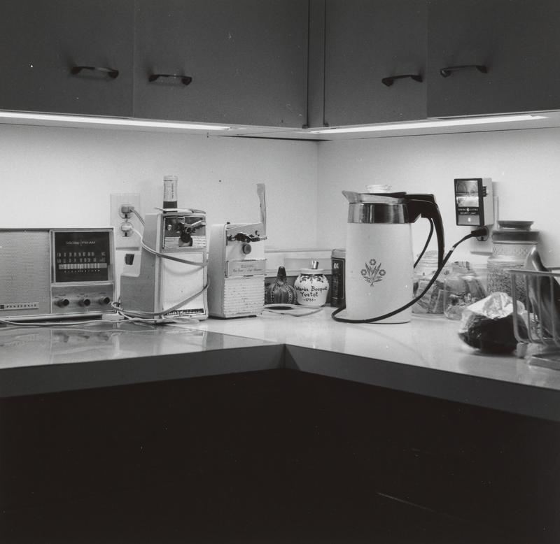 black and white image of a kitchen counter with an electric kettle, radio and two electric can openers