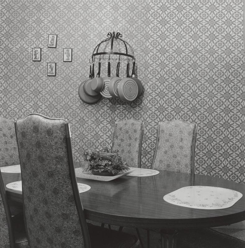 black and white image of a dining table with tall-backed chairs with floral upholstery; wall hanger with hanging pans on wall; four small plaques on wall in ULQ; symmetrical floral motif wallpaper