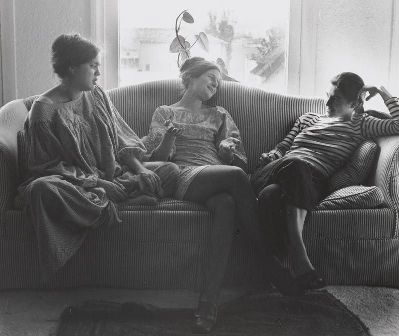 black and white image of three young women seated on a striped couch with a plant in front of a window in background; woman at center holds her hands palm up and looks at woman at right
