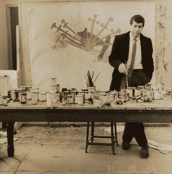 black and white image of a man wearing a dark jacket and a tie, holding a paintbrush, standing behind a table with brushed and paint; partially finished painting in background