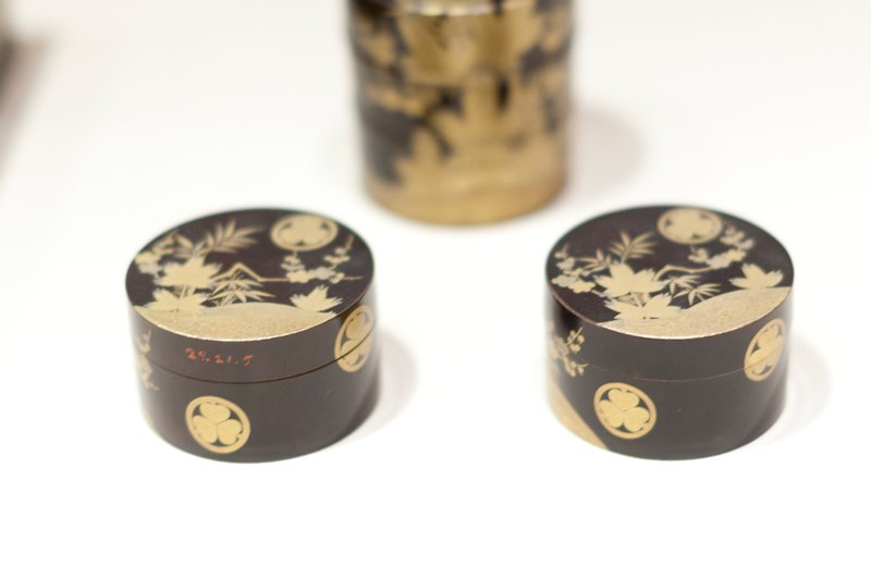 Round covered toilet box of black lacquer decorated with copper and gold in tree and floral motive; bearing three times the crest of the Tikugawa family, three awarum (ginger) leaves, their points together within a circle.