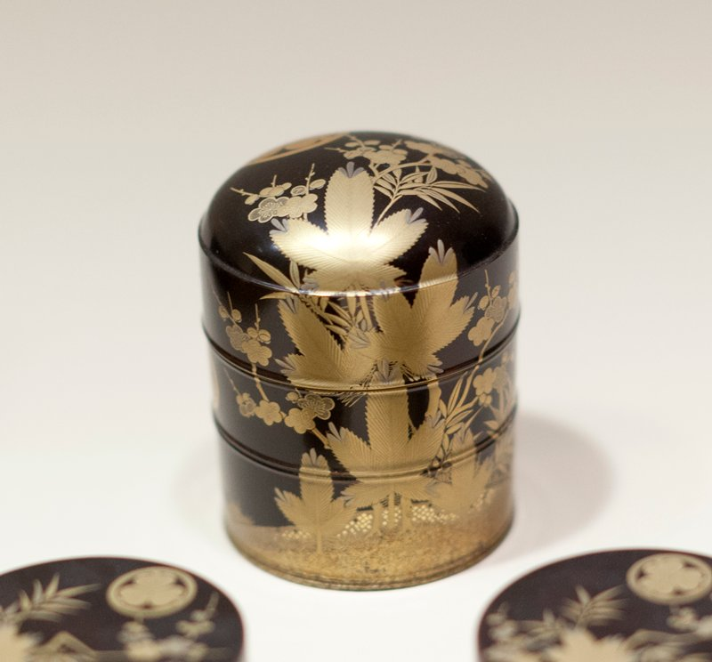 Cylindrical shaped covered toilet box of black lacquer decorated with gold and copper in tree and floral motives; bearing three times the crest of the Tokugawa family, three asarum (ginger) leaves, their points together within a circle.