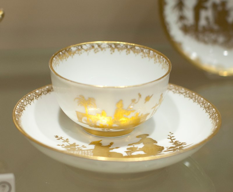 Teacup, ceramic, cat. card dims diam 3-1/8 x H 1-3/4' Cup and saucer; white ground with gold Chinese figures; no handle on cup.