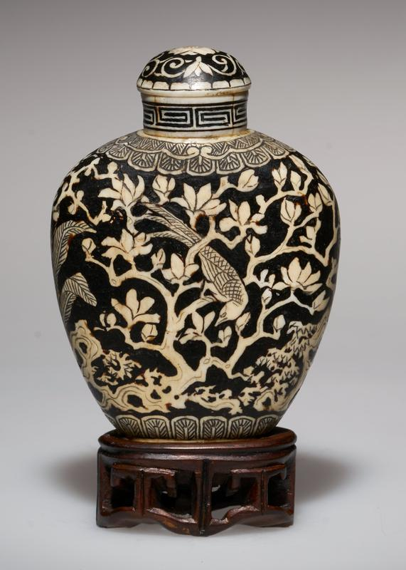 ivory, overlaid with black lacquer; ivory top; lacquer carved; design- two ladies in a garden; other side Pheasant in a Magnolia Tree; pheasant is the emblem of beauty; to the Chinese, magnolia suggests the smile of the Maiden; the Magnolia usually accompanies beautiful women