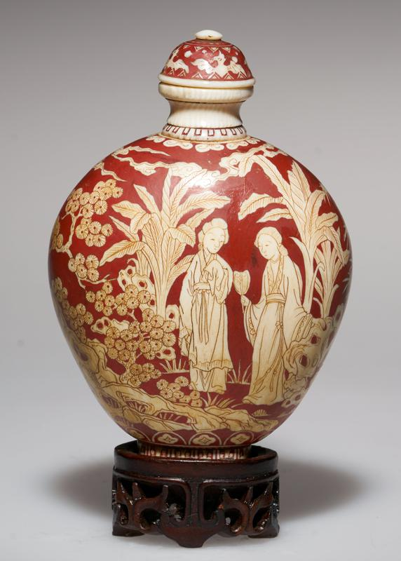 ivory, overlaid with red lacquer; ivory top; design etched in lacquer; charming figures and scenes; the Pine symbolized long life; the Lotus guards against Evil Spirits; the Bat, Symbol for happiness