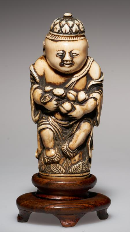 carved figure, with cap as stopper; holding peaches