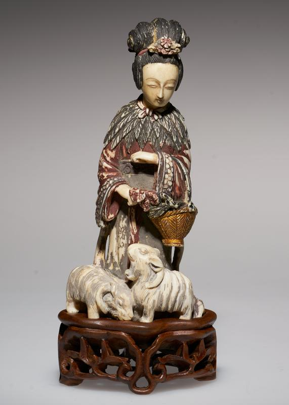 carved figure, carrying flower basket