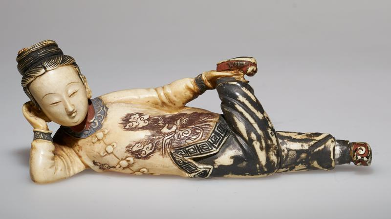 carved ivory figure; spoon attached to the foot