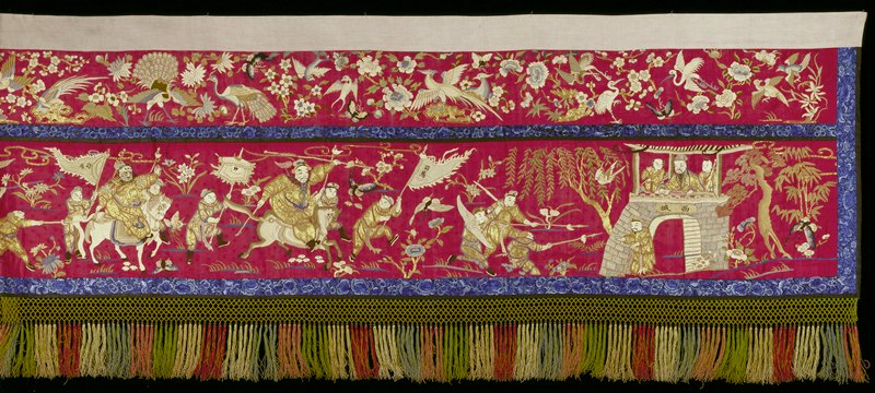 Temple banner of deep red satin embroidered in silk and gold thread with men carrying banners and on horseback. In the lower panel and in the upper panel herons and flowers. Finished with a narrow border of closely embroidered blue flowers and at the bottom with colored silk fringe. Lined with cotton.