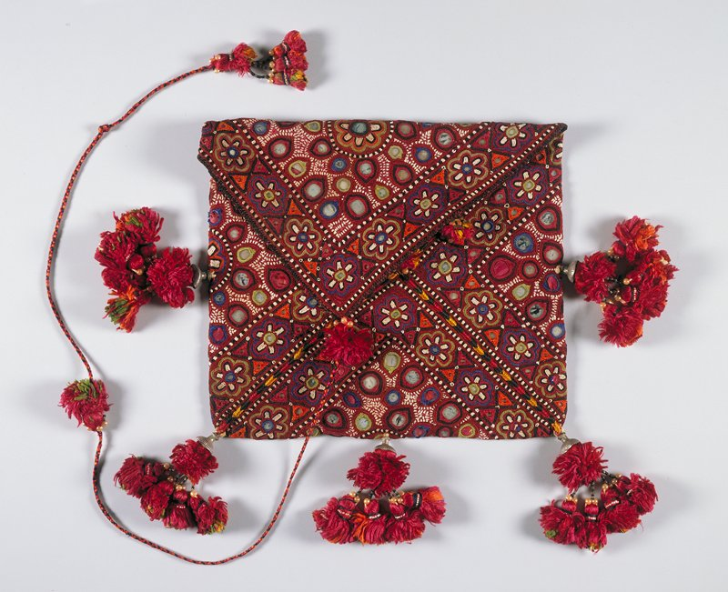 Envelope-shaped pouch of purple silk embroidered all over, and encrusted with mirrors. Ornamented at bottom and both sides with bunches of tassels.