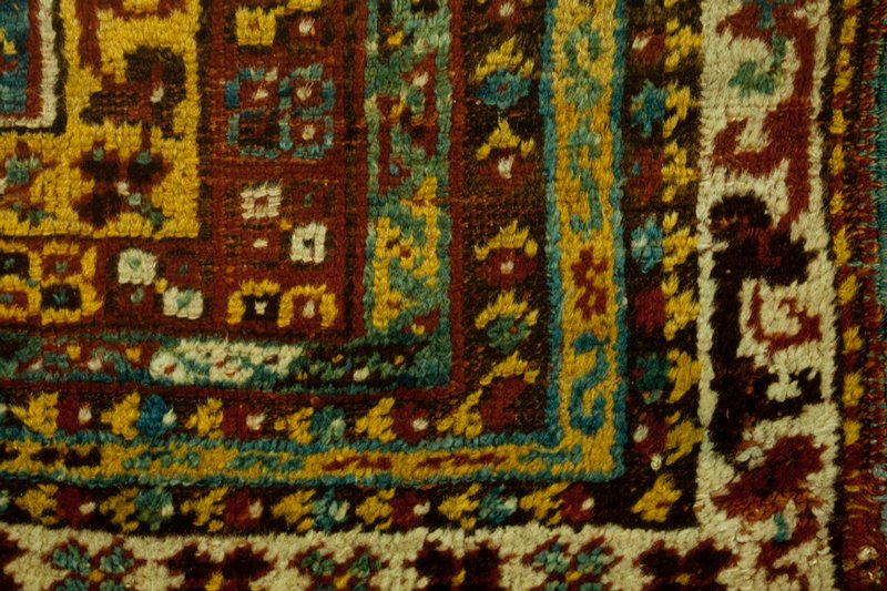 Prayer rug, Kuylah type, with blue prayer niche. The yellow spandrel above the arch is extended down on either side of the niche and beneath it. Seven borders of about the same size, but in various colors, henna, green, brown, yellow and white. The prayer field is covered with flowers, outer and inner borders carry typical Kulah border design. Both ends finished with a wide henna web, and at the top a braided warp fringe. At the bottom end, the fringe is loose. Sides finished wwith an added selvedge of blue wool. The pile is in inch and a half deep. Ghiordes knot. Wool. Cleaned and repaired by Jamgotch, summer 1941.