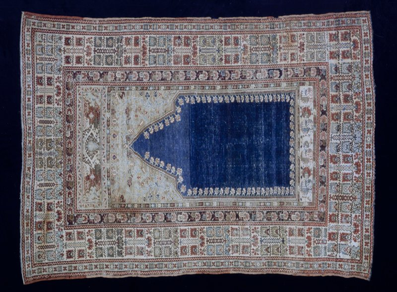 Ghiordes Prayer Rug. The blue prayer niche is fringed with small rosettes in profile. The tan spandrel above the arch carries a vine and flower design that is quuite naturalistic. There are three borders each outlined by a narrow brown guard stripe of saw tooth design. On the ivory ground of the main border conventionalized flowering plants are placed in square formation. The ends are worn. The bottom has a narrow fringe of frayed warp thread, but a narrow web still remains at the top edge. The sides are finished with an added silk selvedge. Ghioredes knot. Warp woolen; woof, cotton.