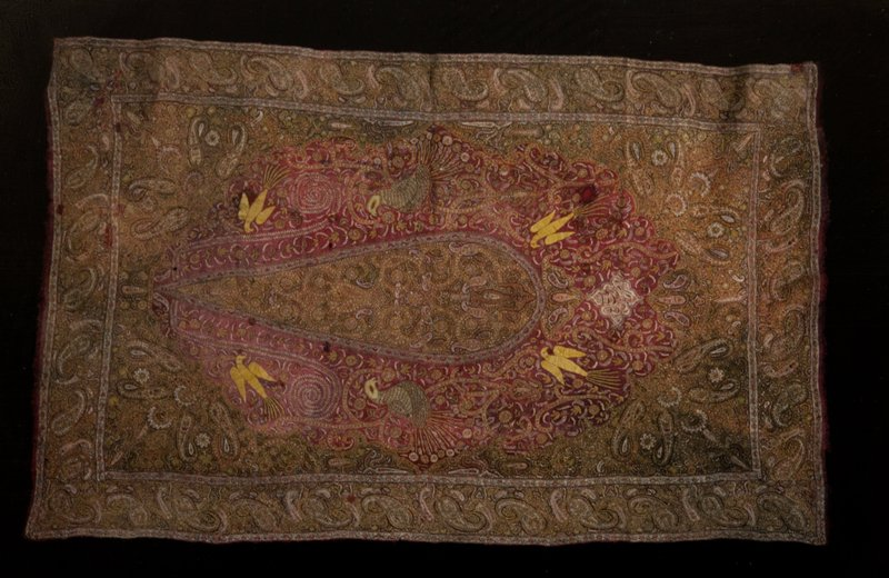 Shawl of red woolen material. Embroidered with tree and birds in center panel which is arch-shaped. The spandrels of the arch and the borders are heavily embroidered with interlacing palmettes. Wool, embroidered.
