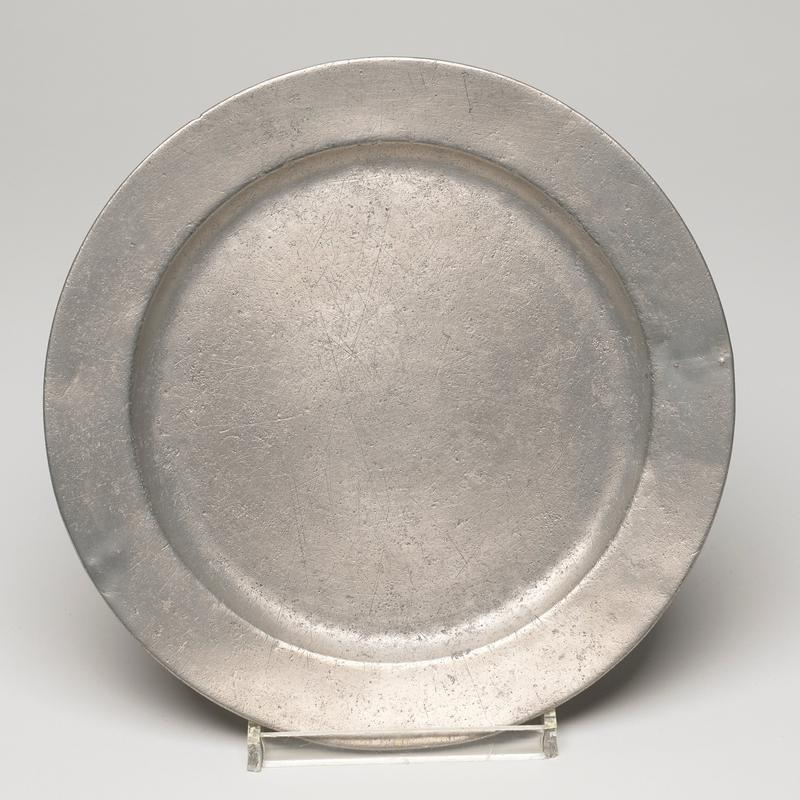round, scratched and oxidized, with a plain rim reinforced by reeding underneath, this type came into favor c. 1750.