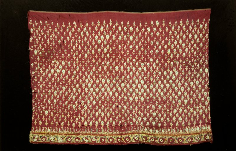 border; piece of red silk embroidered in all over spaced design of stiff single flowers with leaves; chain and laid stitch in green, yellow and white; where the border of sound flower and leaf design is joined to the piece is a series of palmettes outlined in yellow and green alternating with small scrolls; silk on silk