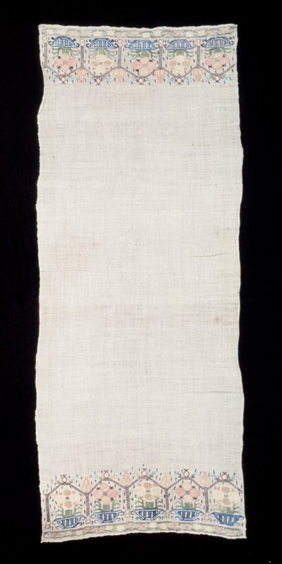 towel, linen, embroidered at each end with a series of five flower and pot motifs seperated one from the other by a narrow frame effect in silk and metal threads, which is in turn decorated at the joining corners by a conventionalized rose and leaf design; blue, rose, yellow and green; silk on linen