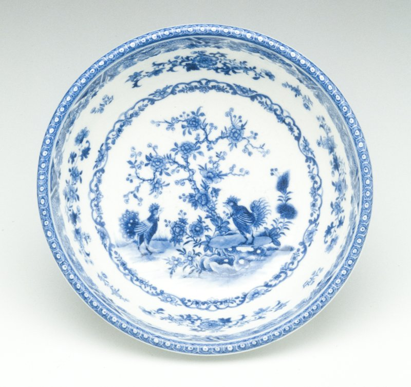 bowl, with raised foot and turned back rim, decorated in underglaze blue; four sprays of flowers on exterior of bowl; interior shows two birds under peony tree (symbol of spring) enclosed in circle of conventionalized arabesques and flowers; sprays of flowers above this; conventionalized repeat motif on rim, with wide band of flowers and designs immediately below