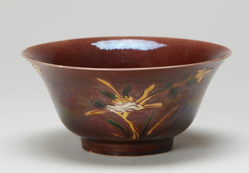 Bowl, flaring rim. Brownish aubergine with incised floral design on outside.