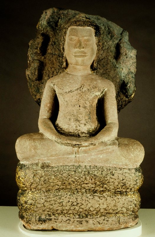 Buddha, figure of, seated on coils of a snake and sheltered by his seven expanded hoods. Monastic garment covers the figure (greatly weathered) leaving right shoulder bare; pendant ears, without jewelry. The Usnisa, or flame, is cone shaped; the hair is apparently plaited. The figure and serpent were originally ornamented with gilding, some of which remains, especially on coils of serpent and rear of his expanded heads. The serpent is in three coils. Provenance Angkor region.