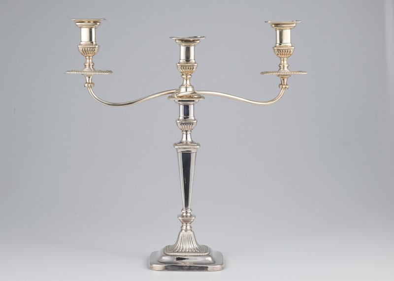 candelabra, one of a pair, oblong, gadrooned base, shaped shaft with gadrooned moulding, and two arms curving out from square gadrooned base of central socket