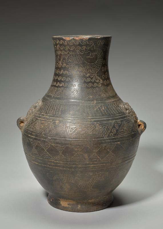 vase, pottery, Hu pear-shaped body, imitation of a bronze type, as is proved by the presence on the shoulders, of two animal heads with loops for pendent rings; The decoration expressed in incised line, combines geometric patterns with stylized tiger forms on a black surface.