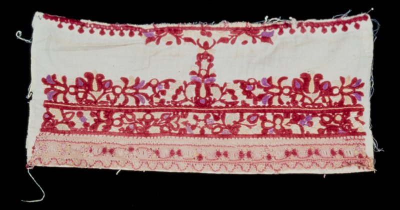 piece from sleeve, embroidered in shades of red, beige and pruple; a band of pinkish lace on the hem; the design is made up of leaves, round spots and conventional flowers