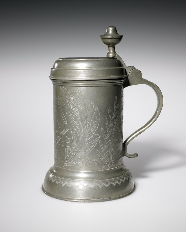 tankard, shallow domed lid and modified ball thumbpiece set on stem, truncated convex base with decorated geometric band in wriggled work, drum ornamentated with leaf sprays and, in front, a set of tools