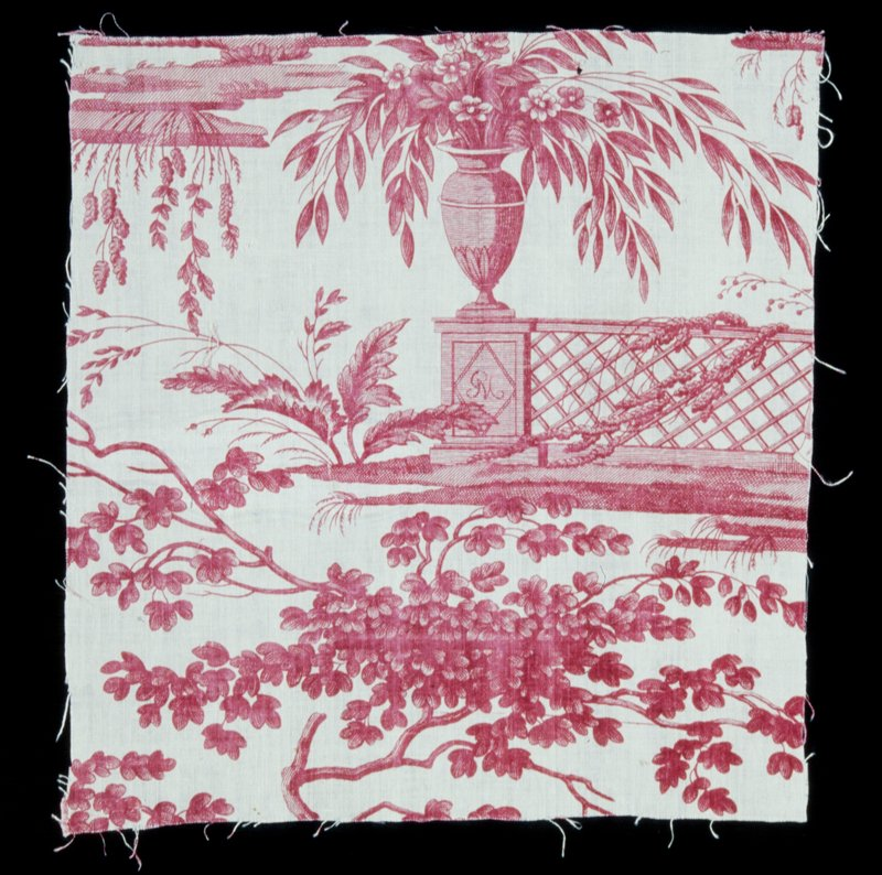 Toile, fragment, copper plate print in rose, from Le Carrousel design. The motif is a flower-filled urn on a vine-clad, trellised balustrade. On the face if the column on which the urn stands is the monogram in a lozenge shield. Below and to the left, clumps of leafy branches.