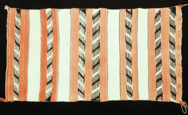 rug, Navajo, made up of horizontal stripes of coral and pale salmon color; the coral stripes carry bands of double comb motifs in brown on pale salmon ground; the stripes are set off from each other with narrow bands of triple dot design; edges overcast; tassels at corners