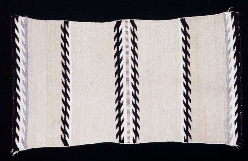 rug, Navajo, sand-colored with bands of double saw-tooth design in black; sides overcast; in the center of the rug a narrow band of vertical lines in tan separates two of the saw-tooth motifs