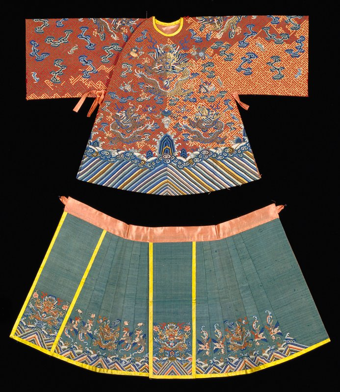 42.50.1,.2 Imperial k'ossu coat and skirt. Coat has gold fretwork meander on an apricot ground, nine 5-clawed dragons, clouds, and eternal sea at bottom. No cuffs, neck bound. Green pleated skirt with eternal sea motif at bottom. The diminutive size of this costume indicates that it was designed either for an idol in an imperial temple or for a doll.