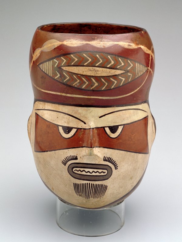 Jar in the form of a man's head painted in polychrome to represent a mummy mask. Top of head draped in a turban. Rounded bottom, stand.