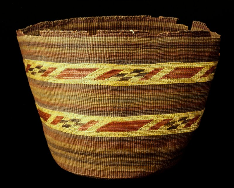 Deep round basket of plain twined weaving with false embroidery. The weaving and foundation are probably spruce root, and the false embroidery is dyed grasses. The design consists of successive stripes of purple, red, orange and green. There are two bands of false embroidery, which consist of parallelograms and coyote tracks in red and brown against a natural background.