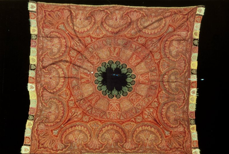 Square Shawl, hand-loom woven , of patchwork. The design of spreading circles, carrynig paired cones and floral and leaf patterns, is bordered by a wide band of interlocking arch.