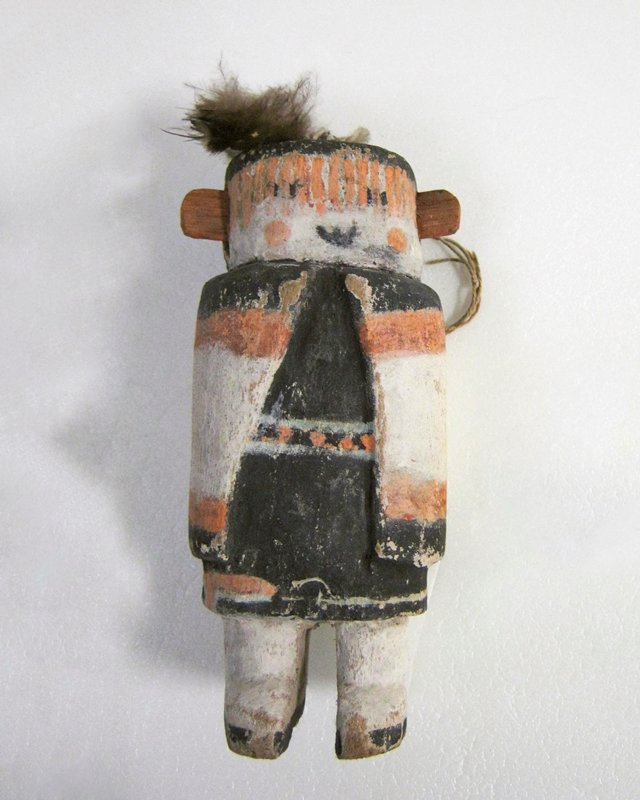 Hopi ceremonial doll, painted; black and white with orange decoration; flattened round head with top-knot of feathers and projecting ears; arms not indicated under cloak; twentieth century