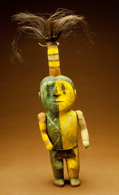 Hopi ceremonial doll, wood, with half of body painted yellow, half green; doll wears a half loin cloth of leather front and back; movable arms, slit mouth, painted eyes, and long top-knot head-dress terminating in a spray of horse's hair