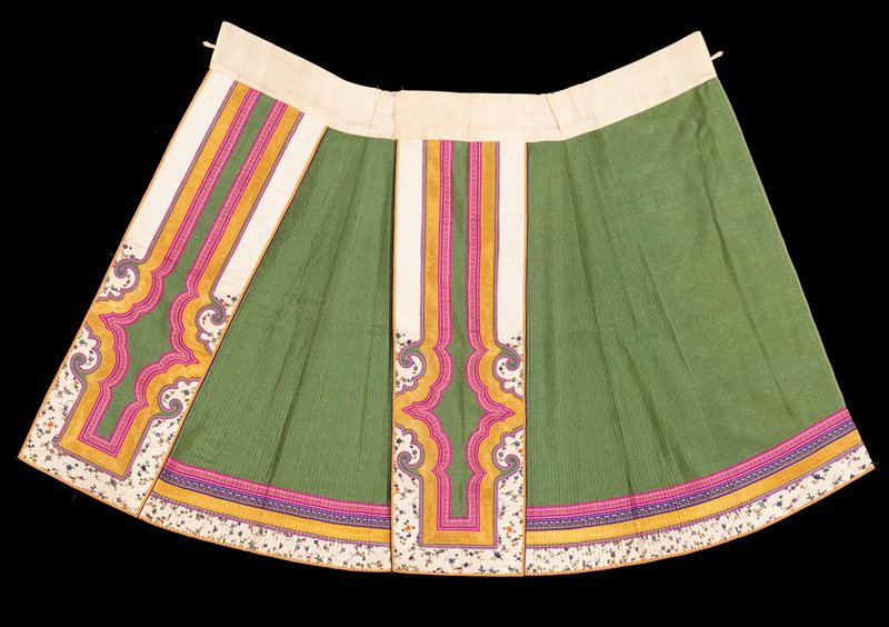 Skirt of patterned green gauze with stitched accordian-pleated side sections. Main panels decorated with an elaborate shaped triple border the outer border of white silk embroidered with small sprays of flowers in loop stitch in shades of blue, green, violet, pink, orange and red; middle border of gold silk braid; inner border magenta silk braid with stylized flowers. the bottom of the skirt has four borders three corresponding to those of the panels and one of purple silk braid with stylized flowers. No lining.
