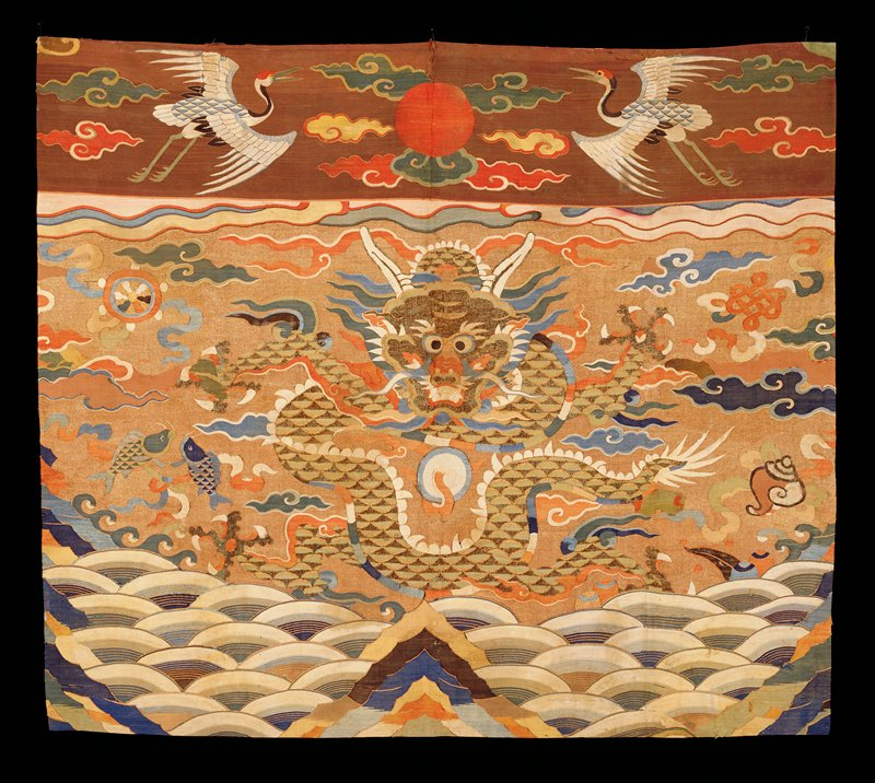 Altar Frontal of gold kesi with large seated, four-clawed dragon in green, partially woven with peacock feathers. In the field are loose, fat clouds, and Buddhist symbols in shades of blue, green, brown, brick-red, tan, and yellow. Below, the waves and sacred Mountain of the Eternal Sea. Note cloud restorations of finer kesi. In upper valance section of brown kesi, set off from main field by an uneven band of watery, run-together clouds, appear the sun disc flanked by two white cranes in a cloud field. Colors include red, green, yellow, and blue. Lining of strips of bright blue satin damask of medallion design.