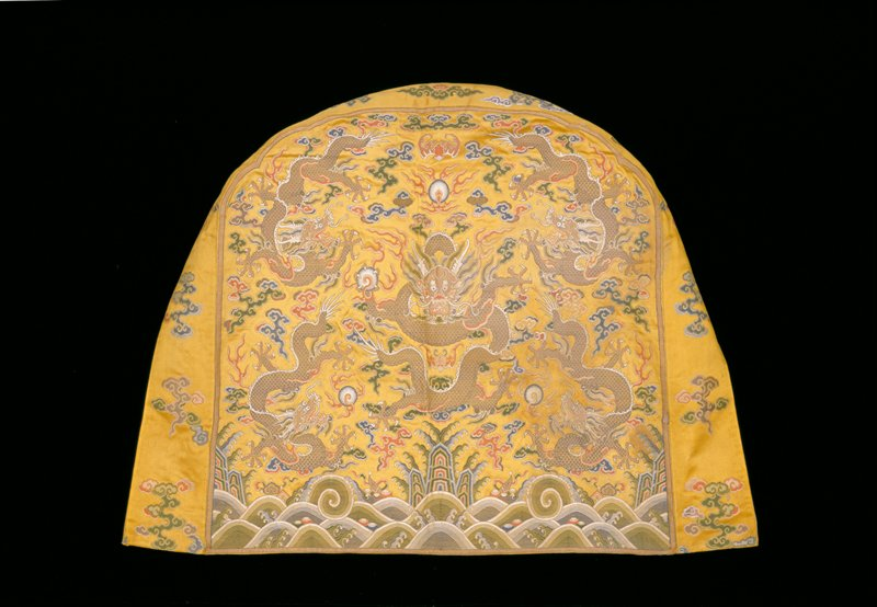 Shaped throne-back cover of imperial yellow satin brocade. In a field with loosely-drawn clouds and a bat, five five-clawed dragons in gold the large central one seated, the four surrounding ones in profile. Below, the Eternal Sea motif, with deeply rolling waves dotted with symbols of the Eight Precious Things. Colors include shades of blue, red, green, and pink. Boxed border of the yellow satin brocaded with a design of spaced, loosely-drawn clouds. Seal inscription. Lining of yellow satin.