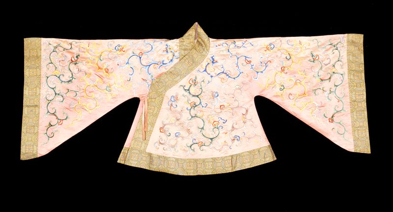 Theatrical short coat of pale coral colored satin embroidered with slender, sinuous dragons in shades of blue, violet, green, pink, yellow, orange, and red. Satin stitch with outlines of couched gold thread. Wide border, collar, and cuffs of polychrome brocade in a design of floral medallions. Note triangular shape of sleeves and drawing of dragons. Lining of thin lavendar silk. This probably a woman's coat, but worn by male actor as is customary in China.