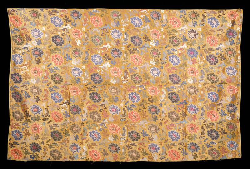 Large Hanging of golden tan satin brocade composed of two widths seamed up the middle. All-over design of peonies, lotus, and trailing leaves in shades of blue. green, magenta, pink, mulberry, violet, grey, pink, brown, and yellow with gold. Lining of yellow raw silk. Inscription. Cf. 42.8.137,.138 for same general type of pattern.