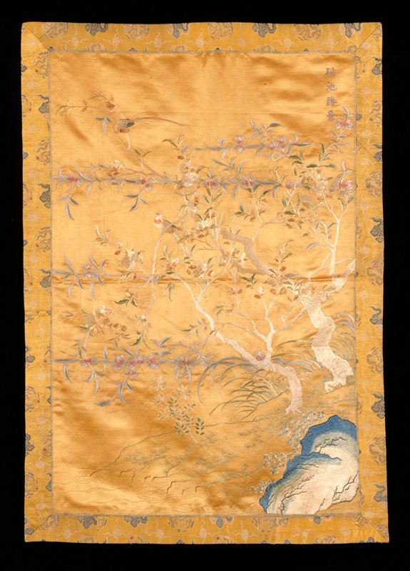 Picture hanging of embroidered gold-colored satin. the design represents a landscape in which wide-branching floral trees grow from a low hill. Two birds perch on the branches. In the lower foreground grow branches of pine, and to the right is a mountain. Embroidery in very fine satin stitch in shades of blue pink, green, pale tan, light rust, and eggshell. Border of Yellow satin brocaded in colors and gold of dragon-medallion and cloud design. At upper right of picture is a four-character inscription embroidered in blue silk. Lining of mustard yellow raw silk. Former Classification: Textiles - Tapestry