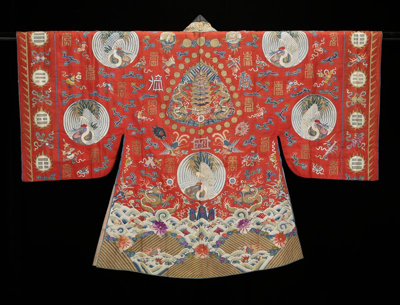 Taoist Priest robe (theatrical ?) of red k'ossu weave. Design includes five large medallions containing the white crane with sacred fungus; loose clouds, phoenix, sun and moon symbols on shoulders, five-clawed gold dragons, Taoist symbols and numerous good-luck characters in shades of blue, green, pink, red, yellow, peach and violent purple. In the sleeve bands are medallions with the sacred trigrams, On the back panel a border that is conventional except for the fact the the striped area breaks through the rolling wave area in places. Tight clouds; waves scattered with large blossoms, swastikas, bats, Buddhist, and other symbols. Crane and bat border in front. Long collar band of yellow with swastika fret diaper in blue, bats, cranes, and clouds. Below , on each side, a band of white k'ossu with Foo dog on one side; dragon on other. Lining of coarse pink cotton. Taoist priest robes in k'ossu are rare.