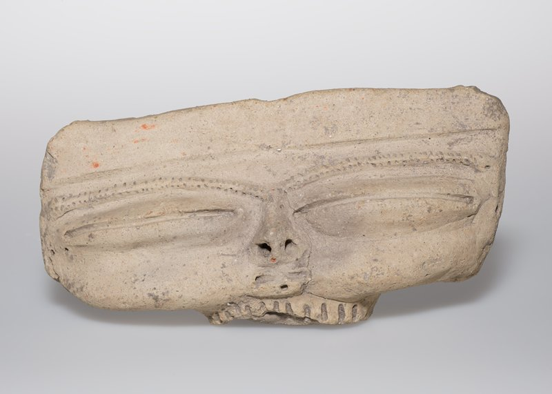 Head, pottery, canoe-shaped, with long, coffee-bean shaped eyes, small nose, pendent cheeks, and a row of teeth indicated by modelling. Eyebrows formed of two rows of incised dots.