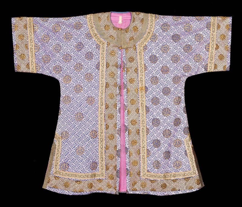 Coat of medium blue brocaded silk with embroidered swastika fret diaper in lavendar silk. Throughout ground medallions of long-life character in couched gold thread. Wide sleeves with a band of black silk with lavendar wastika fret diapr and long life medallions i gold. Inner borde rof pale green satin floral brocade. Collar and border of same, with band of green and gold swastika fret borcade setting collarband off from inner border of pale green brocade. Coat slit at sides and lined with thin lavendar silk.