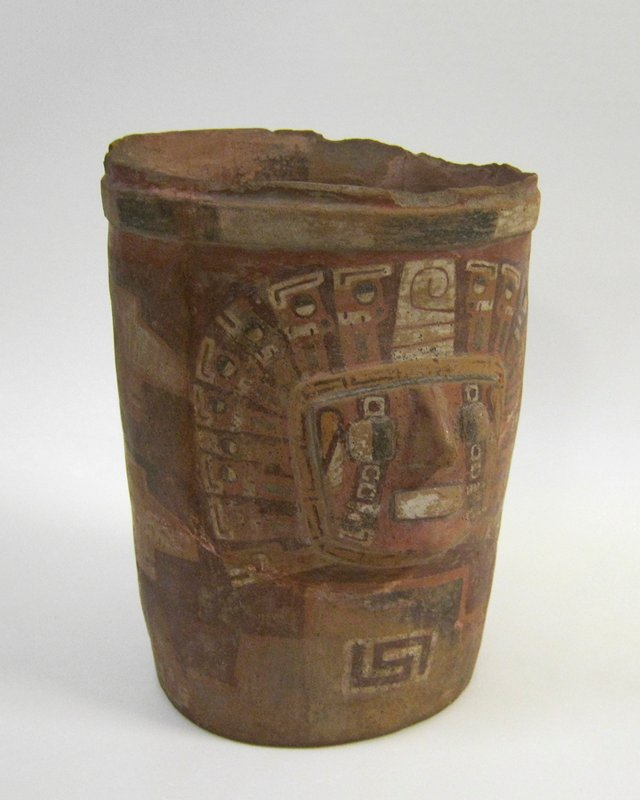Jar, straight-sided, decorated on one side with a head representing the god Viracocha. The square face, projecting from the surface, has nose, eyeballs, and rectangular mouth in relief. The god wears an elaborate headdress with a projecting border of puma heads. The headdress and face, including a line of stylized tear drops falling from each eye, are painted in black, brick red, cream, and buff on a ground of darker red. The back of the jar is decorated with four vertical rows of crudely drawn heads in profile painted in brick red and buff. Design and workmanship primitive. Jar restored.