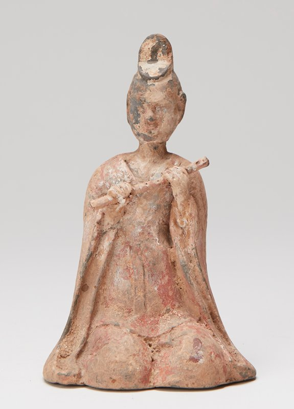 Figure of Buddhist priest (?) playing flute.