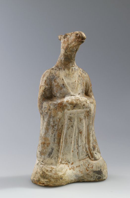 Zodiacal figure in form of man with head of horse. Representing God of the Constellation Hsing. Grey earthenware with white ground. Painted with flesh-coloured pigments; Daoist symbol for the principle 'The Creative; Heaven' (Ch'ien =) see cat. card for better description.
