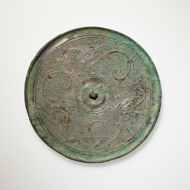 Mirror, round, with dragons on interlocking 'T' ground. Lo-yang type
