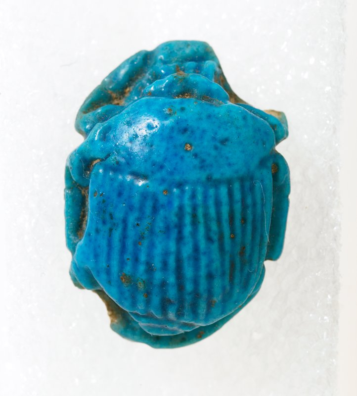 Scarab, faience beads, front R/rear L damaged. Blue-glazed; edges broken at front right and rear left sides.